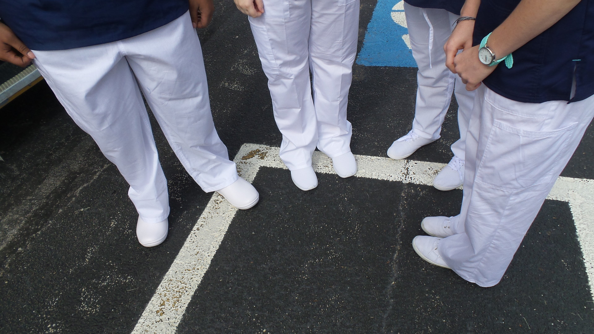 Students display white uniform shoes