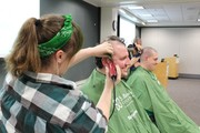 KACC Student Shaving hear of CSL Behring staff member for St. Baldrick's fundraiser