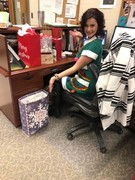 Jamie Posing with several holiday gifts sitting at her desk.